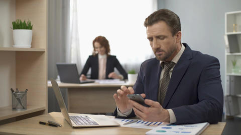 Man in suit checking cellphone, typing data on laptop, office work, distraction Footage