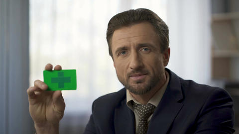 Middle-aged man holding card in green color in hands, future retirement plan ビデオ