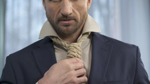 Handsome man fixing death rope on neck instead of tie, marriage of convenience Footage