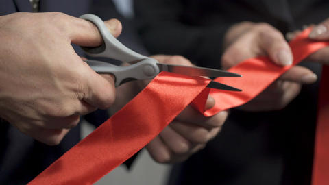 Top manager cutting red ribbon, shaking hands with partner, project cooperation Footage