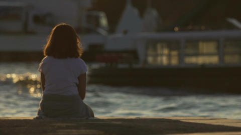 Upset teenage girl sitting on pier alone, peering into distance, loneliness Footage