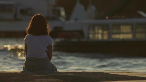 Upset teenage girl sitting on pier alone, peering into distance, loneliness Footage