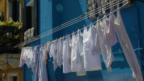 Clean clothes fluttering in wind, hanging on bright blue colored house facade Footage