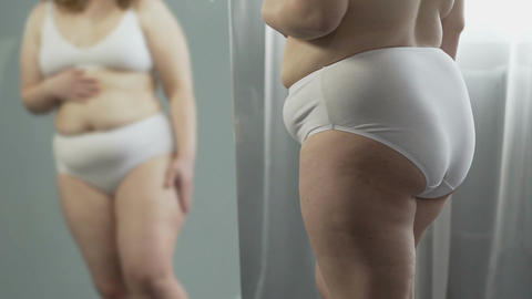 Chubby female turning from side to side in front of mirror, touching her body Live Action