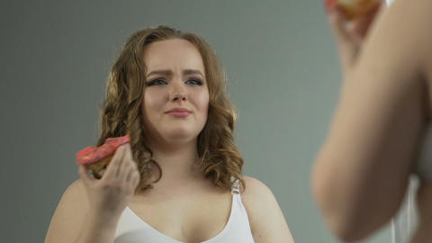 Depressed overweight girl looking at body in mirror, eating donut in despair Live Action