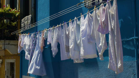 Fresh laundry hanging on rope in Italian city, everyday life on Burano island Footage