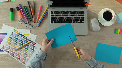 Professional wedding decorator cutting blue paper, creative work, handcraft Footage