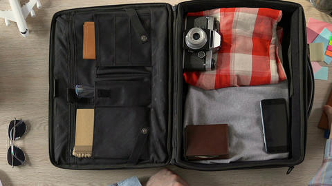 Traveler packing his suitcase, putting purse, passport with tickets and money Footage