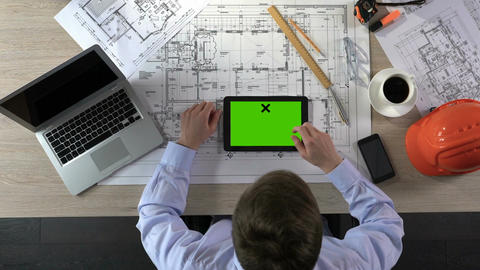 Professional architect viewing apartment photos on green screen tablet, top view Footage