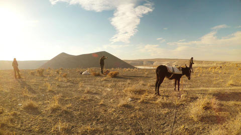 The shepherds are preparing tea near the mule attached to the background of the  Footage