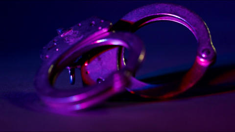 Handcuffs with Red and Blue Police Lights and a Bokeh Effect Footage
