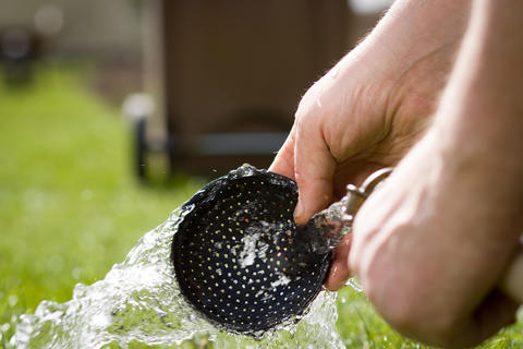An old hand of active senior washing an equipment of gardening d Photo