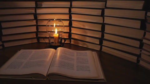 Book and candle on the table on the background of old books Footage