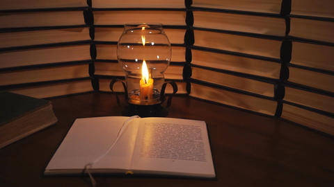 Open book and a burning candle Live Action