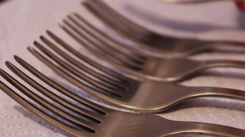 Stacks polished steel forks on a white napkin Footage