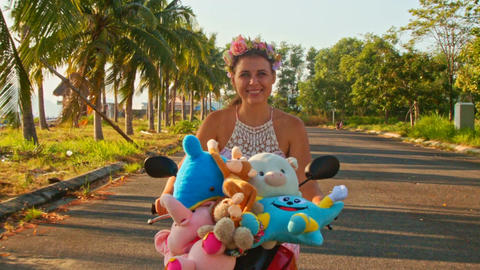 Closeup Nice Girl in Garland Rides Moped with Toys Footage