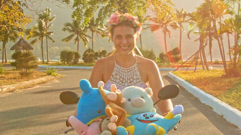 Closeup Smiling Girl in Wreath Rides Moped with Toys Footage