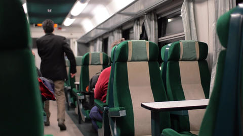 Man crosses a passenger coach among banks with green trim to get to the toilet Footage