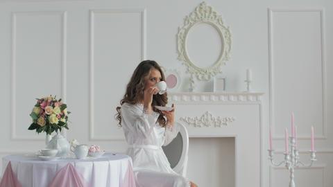 Beautiful woman in bathrobe drinking coffee Footage