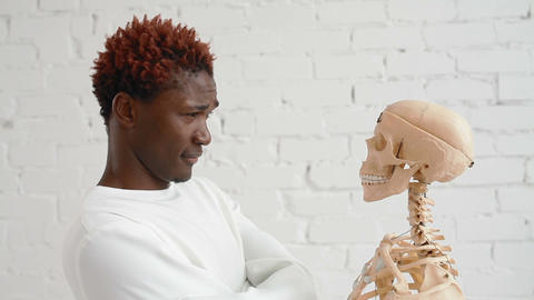An insane black man wearing a straitjacket dance and looking at human skeleton Footage