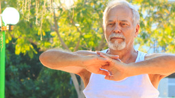 Old Man Does Morning Exercises Stretches Fingers in Park Footage