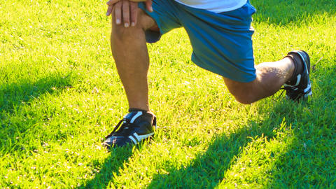 Man Does Morning Exercises Squats on Left Right Knee on Grass Footage