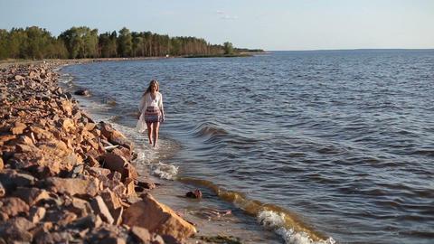 Carefree beautiful woman strolling seashore Footage