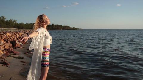 Girl takes deep breath enjoying fresh air on beach Live Action