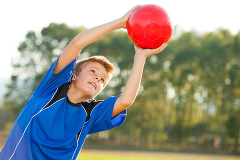 Young boy catching red ball outdoors Photo