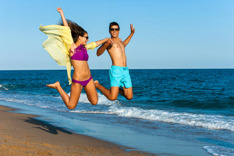 Crazy couple jump on beach Foto