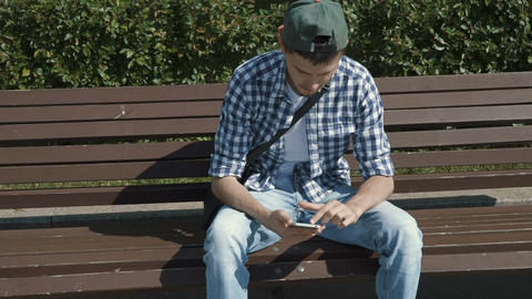 Young handsome man browsing internet on smartphone Footage