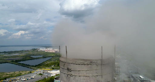 Close-up of an industrial pipe with smoke on a city background. Aerial Footage