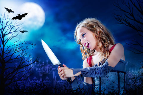 Young vampire with knife at full moon フォト