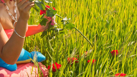 Closeup Girl Squats in Green Grass Smells Roses Footage