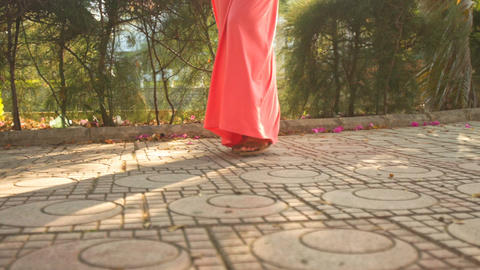 Girl in Coral Dress Steps Ahead on Pavement Footage