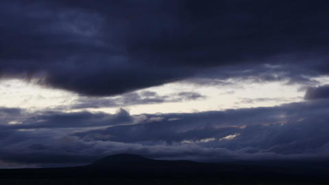 Time lapse of dark dramatic clouds moving over hills Footage