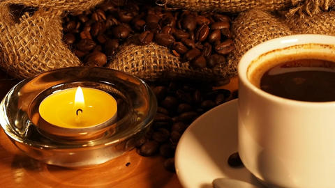 romantic background with candles, a cup of coffee and coffee beans in a bag Footage