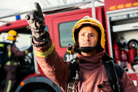 Anxious fireman pointing at fire Photo