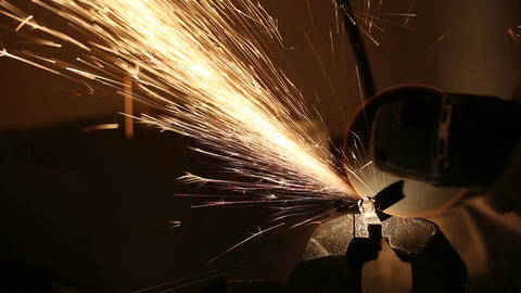 Sparks fly while the man cutting a metal rod with a grinding machine Footage