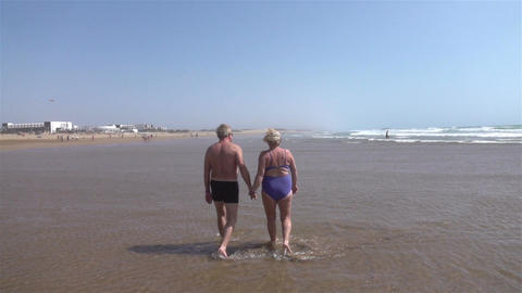 Video of senior couple walking by the ocean in real slow motion Footage