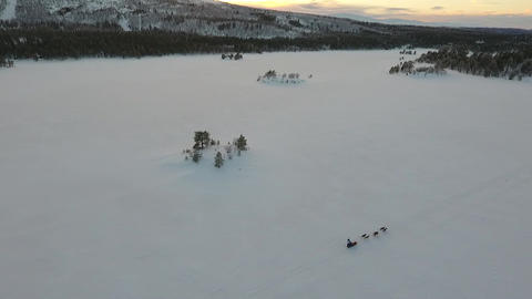 Drone flight over a dog sled crossing a frozen lake Footage