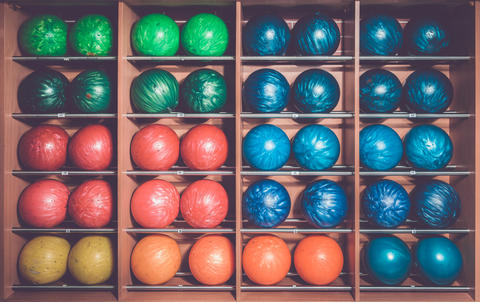 Bowling balls in the rack, sorted by size and color フォト
