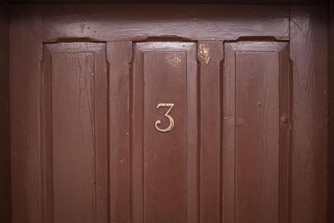 Number three wooden door in an ancient hotel Photo