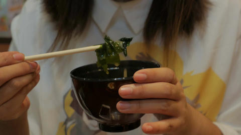 Woman hand eating miso soup with chopsticks Footage
