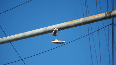 Video of pair of shoes hang tossed telephone wire in 4K Live Action