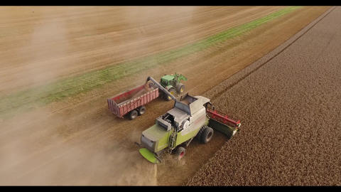 Drone flight over a combine harvester filling wheat on a tractor 画像