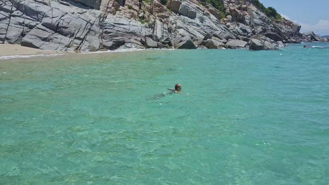Girl Swims in Tranquil Azure Ocean near Rocky Beach Live Action
