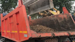 Excavator loads the soil in the truck 画像