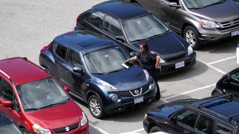 Top shot of parking enforcement officer placing ticket for overtime parking car  Footage