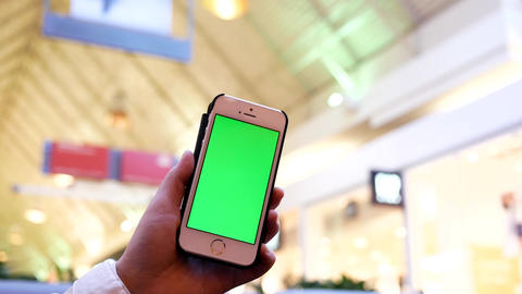 Motion of woman holding green screen phone with blur people shopping inside mall Footage